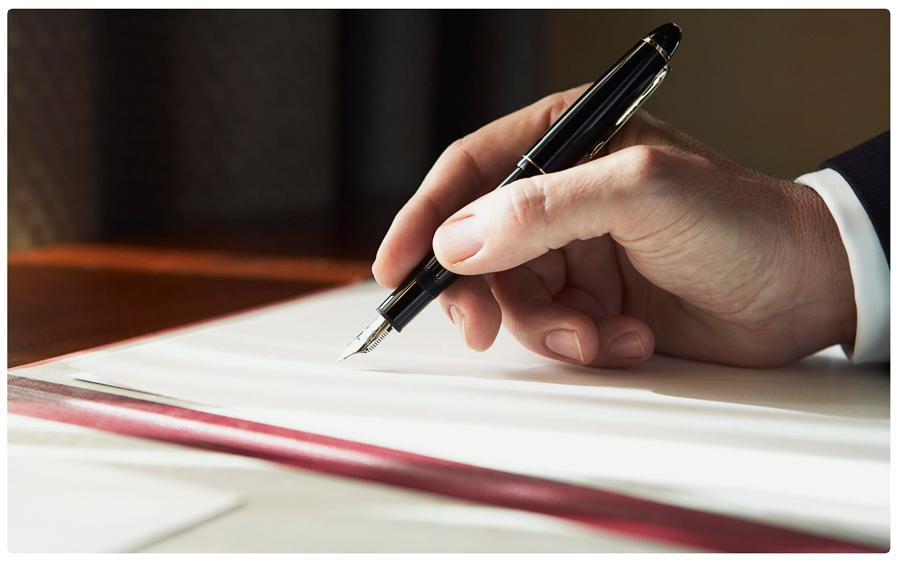 человек пишет на бумаге пером